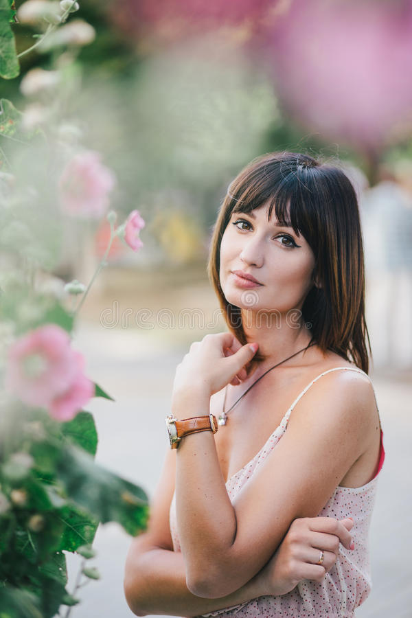Schönheit in einem rosa Kleid, das nahe rosa Blumen aufwirft lizenzfreie stockbilder