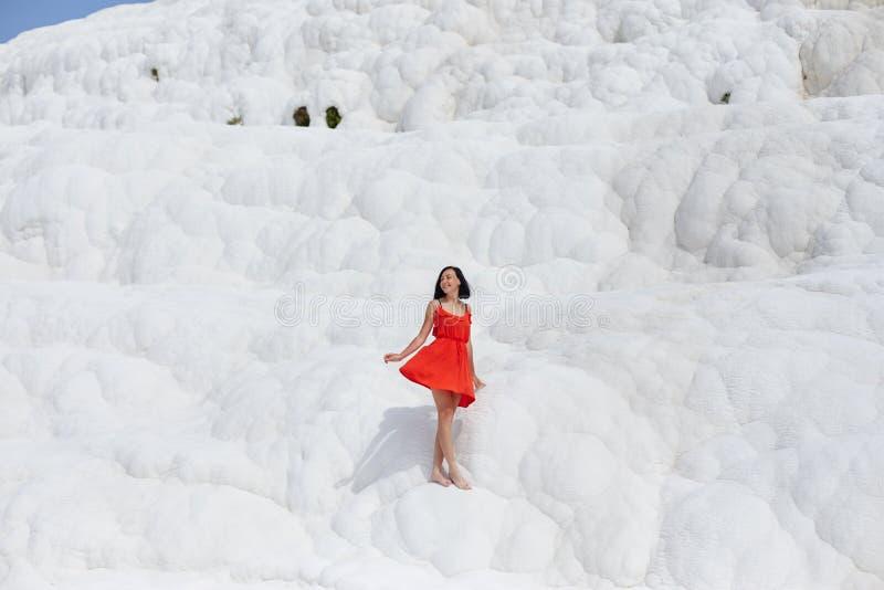 Schönheit in einem roten Kleid steht gegen die weißen Berge Fabelhafte Landschaft, überraschende Natur Mädchen auf einem weißen F stockbilder