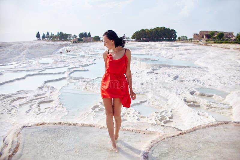 Schönheit in einem roten Kleid steht gegen die weißen Berge Fabelhafte Landschaft, überraschende Natur Mädchen auf einem weißen F stockfoto