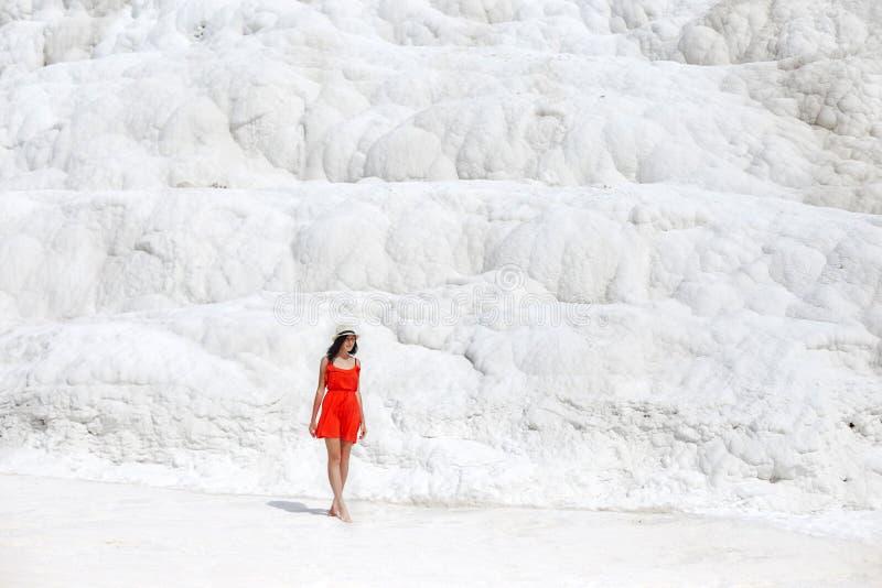 Schönheit in einem roten Kleid steht gegen die weißen Berge Fabelhafte Landschaft, überraschende Natur Mädchen auf einem weißen F lizenzfreies stockfoto