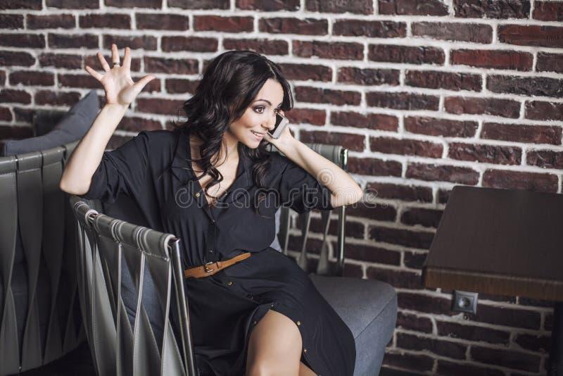 Schönheit in einem Stuhl im Restaurant mit dem Telefon stockbilder