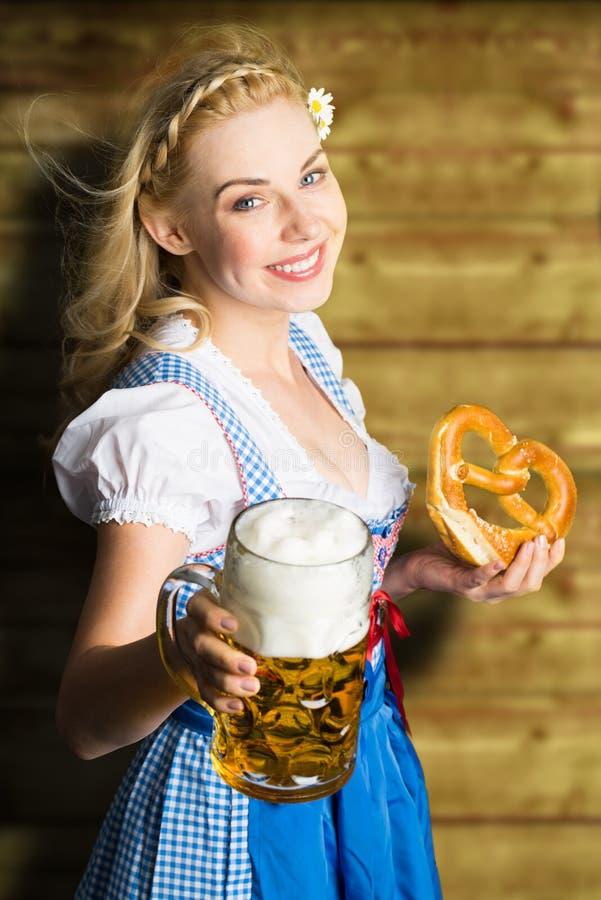Schönheit in einem traditionellen bayerischen Dirndl mit Bier und Brezel lizenzfreies stockbild