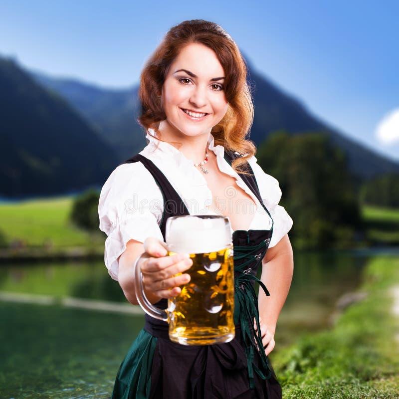 Schönheit in einem traditionellen bayerischen Dirndl mit einem Bier stockfotos