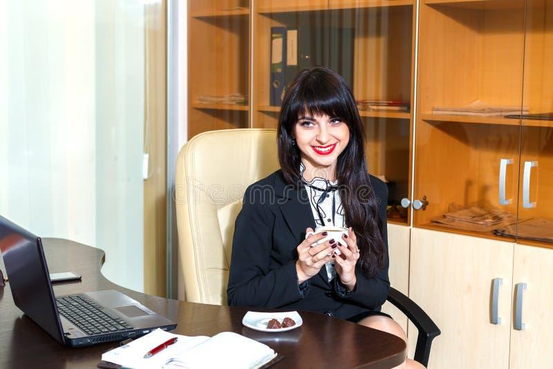 Schönheit im Büro, das eine Kappe des Kaffees hält stockfoto