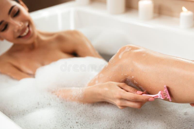 Schönheit im Badezimmer liegt, stillstehend im Bad, das ihre Beine rasiert lizenzfreies stockfoto