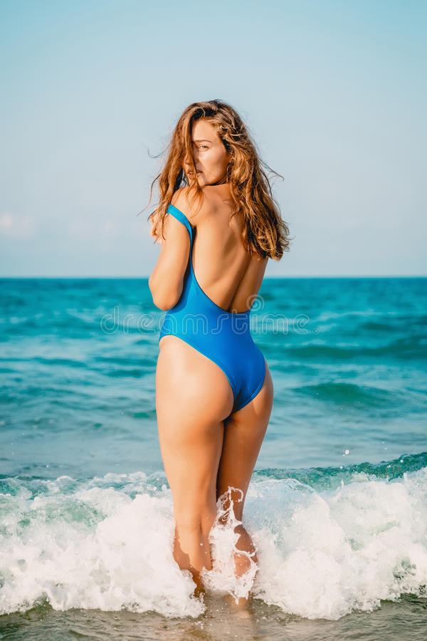 Schönheit im blauen Bikini im Ozean und Betrachten der Kamera stockfotografie