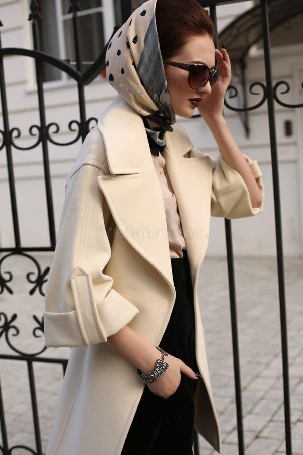Schönheit im eleganten Mantel- und Seidenschal auf Kopf stockfotografie