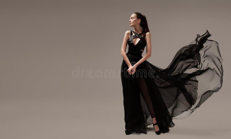 Sch?nheit im gl?ttenden schwarzen Luxuskleid stockbild