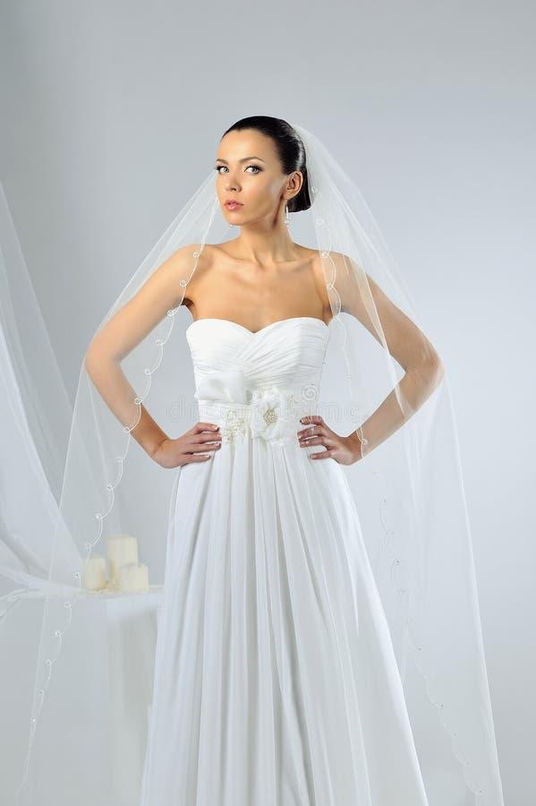 Schönheit im Hochzeitskleid, das im Studio aufwirft lizenzfreie stockfotos