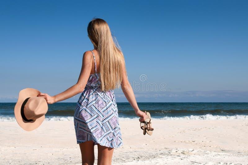 Schönheit im Kleid mit Hut und Pantoffeln auf dem Strand lizenzfreies stockbild