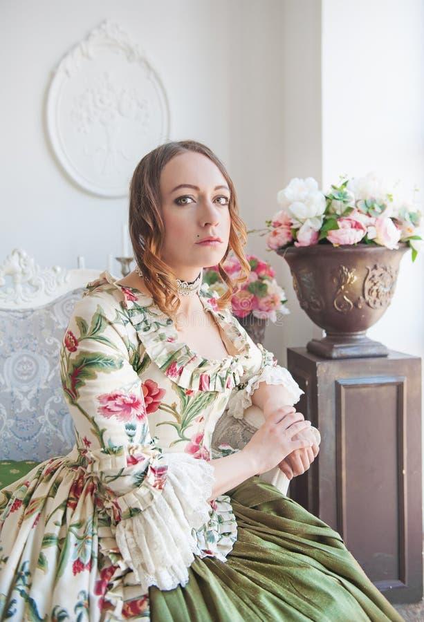 Schönheit im langen mittelalterlichen Kleid, das auf dem Stuhl sitzt lizenzfreie stockbilder