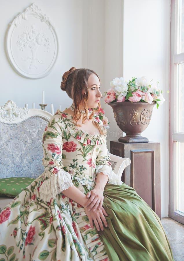 Schönheit im langen mittelalterlichen Kleid, das nahe Fenster sitzt stockfotos