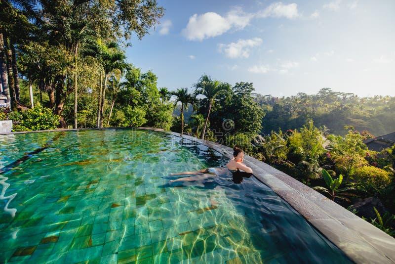 Schönheit im luxuriösen Erholungsort Junges Mädchen, das ein Bad nimmt und am UnendlichkeitsSwimmingpool sich entspannt lizenzfreie stockfotografie