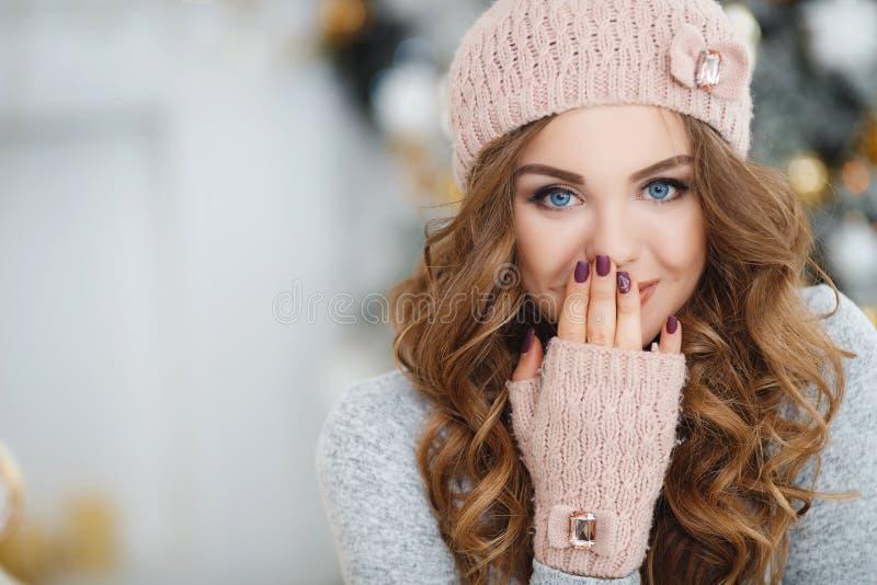 Schönheit im rosa Hut nahe Weihnachtsbaum lizenzfreie stockbilder