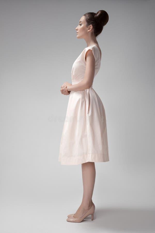 Schönheit im rosa Retro- Kleid Grauer Hintergrund stockbild