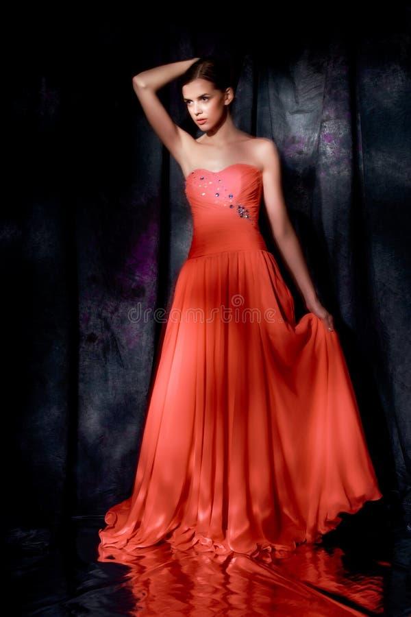 Schönheit im roten Abendkleid auf dunklem Hintergrund lizenzfreie stockfotografie