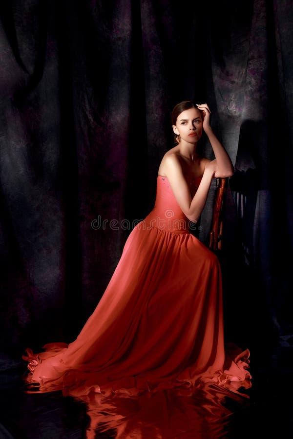Schönheit im roten Abendkleid auf dunklem Hintergrund lizenzfreies stockfoto