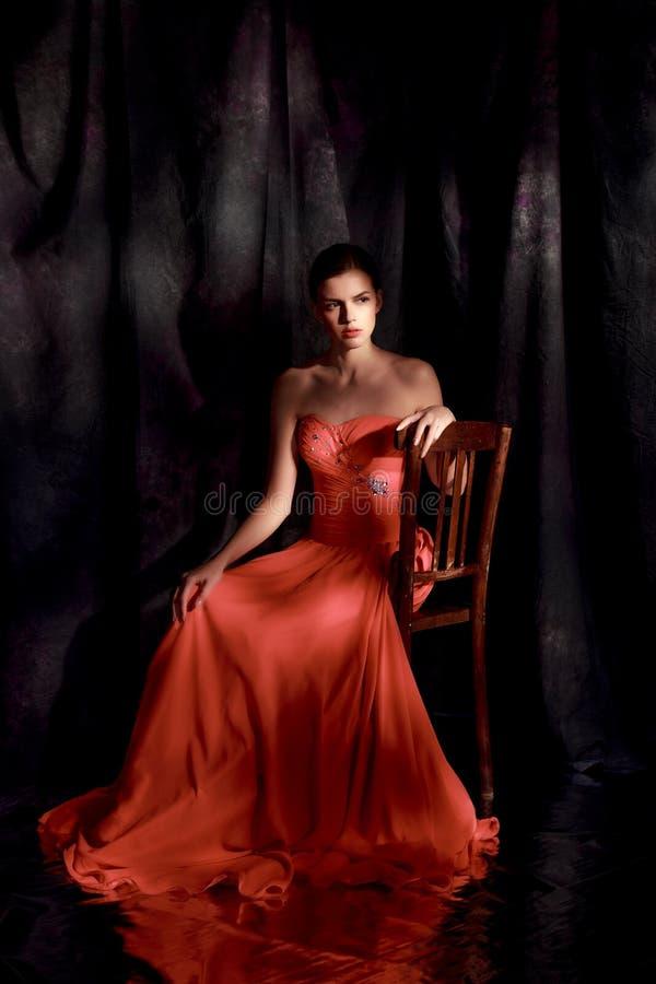 Schönheit im roten Abendkleid auf dunklem Hintergrund stockfotos