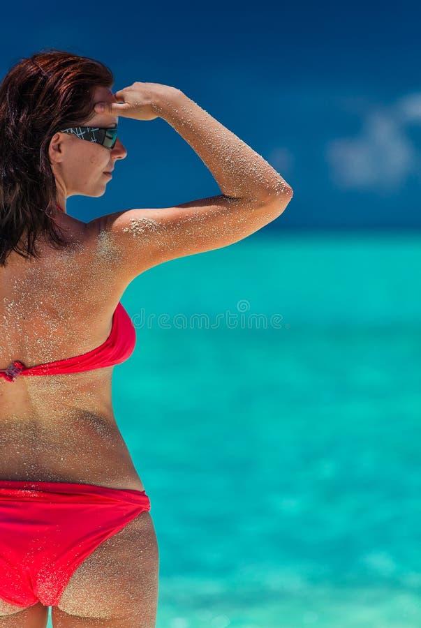 Schönheit im roten Bikini mit sandiger Rückseite auf einem Strand lizenzfreie stockbilder
