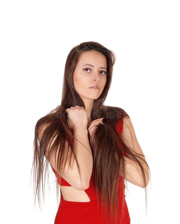 Schönheit im roten Kleid, das mit ihrem Haar spielt stockfoto