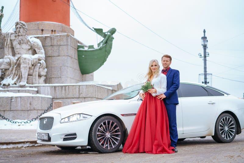 Schönheit im roten Kleid und im Mann, die Stellung im Winter, Hochzeit in St Petersburg aufwirft lizenzfreie stockbilder
