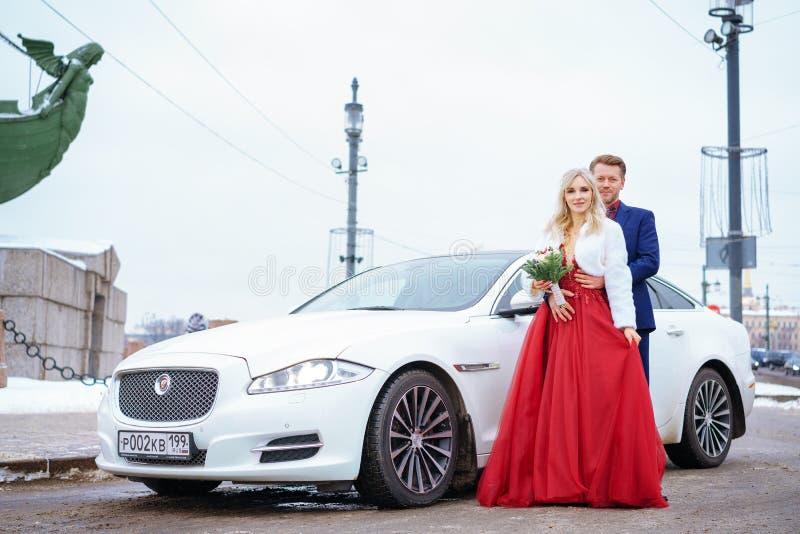 Schönheit im roten Kleid und im Mann, die Stellung im Winter, Hochzeit in St Petersburg aufwirft stockfoto