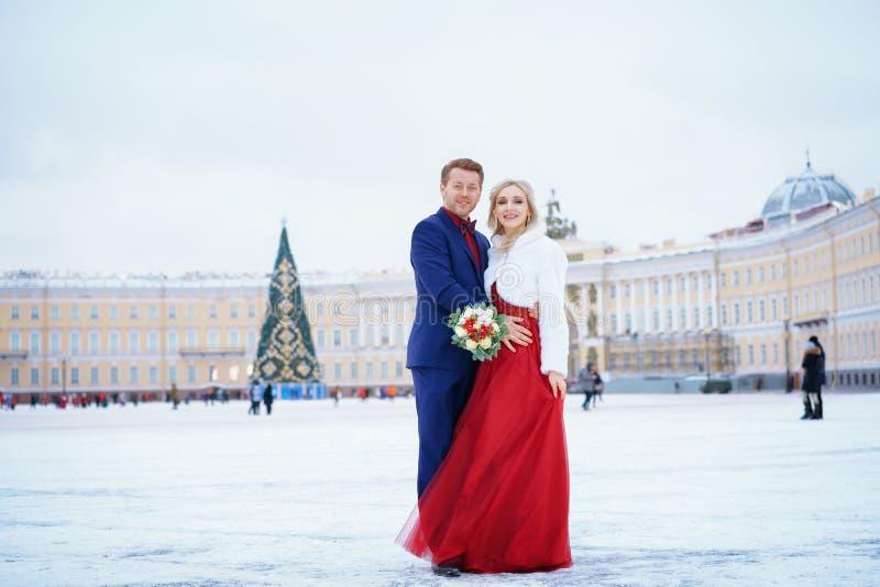 Schönheit im roten Kleid und im Mann, die Stellung im Winter, Hochzeit in St Petersburg aufwirft stockfotografie