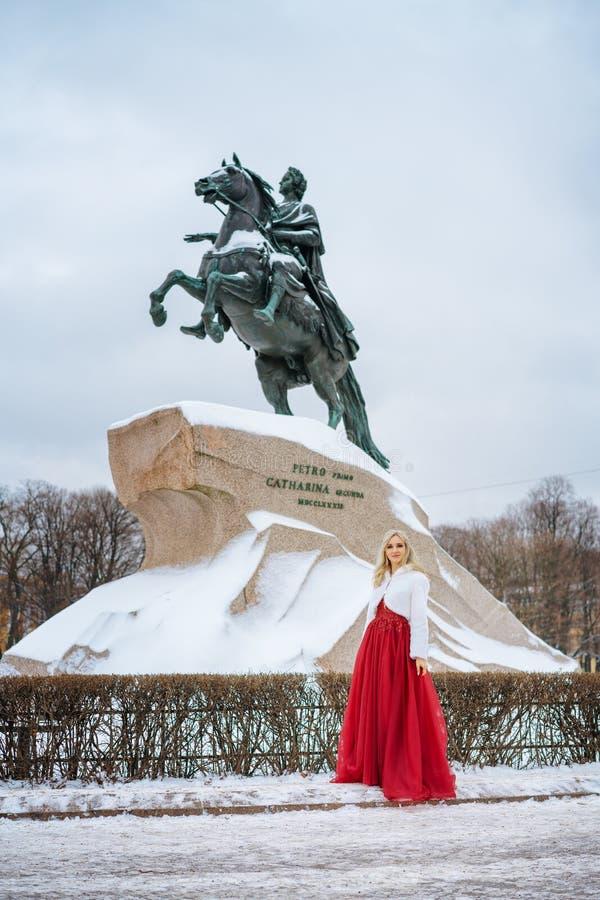Schönheit im roten Kleid und im Mann, die Stellung im Winter, Hochzeit in St Petersburg aufwirft stockbilder