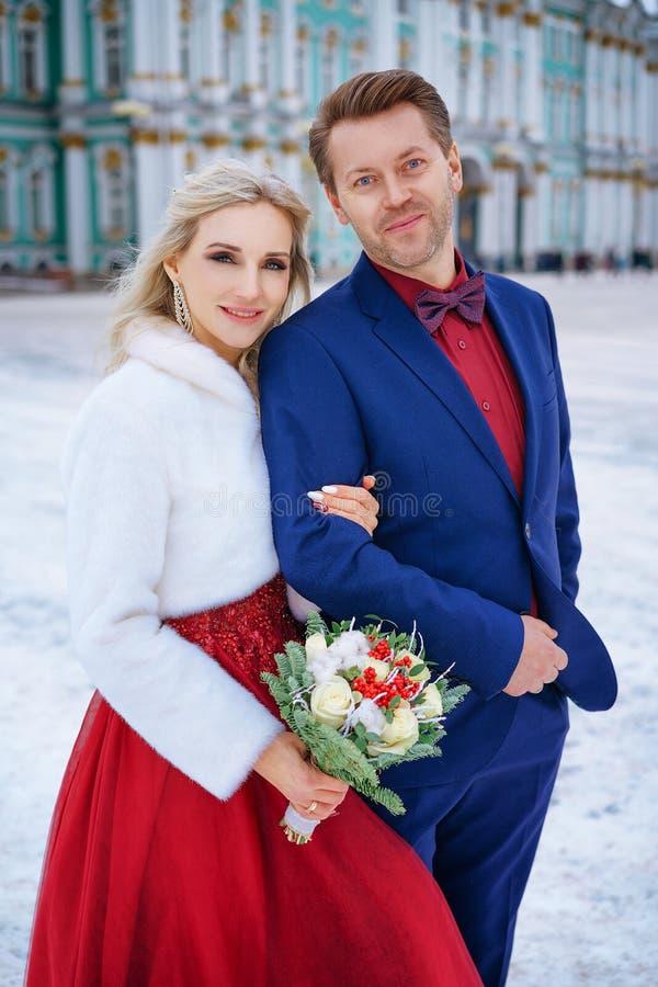 Schönheit im roten Kleid und im Mann, die Stellung im Winter, Hochzeit in St Petersburg aufwirft lizenzfreie stockfotos