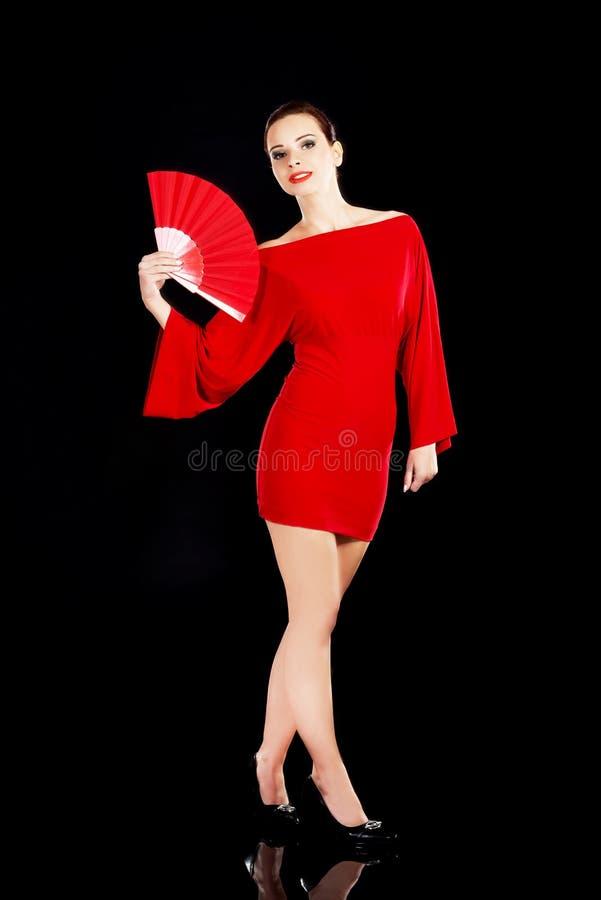 Schönheit im roten sexy Kleid mit Fan. stockfotografie