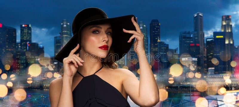 Schönheit im schwarzen Hut über Singapur-Stadt stockfotografie