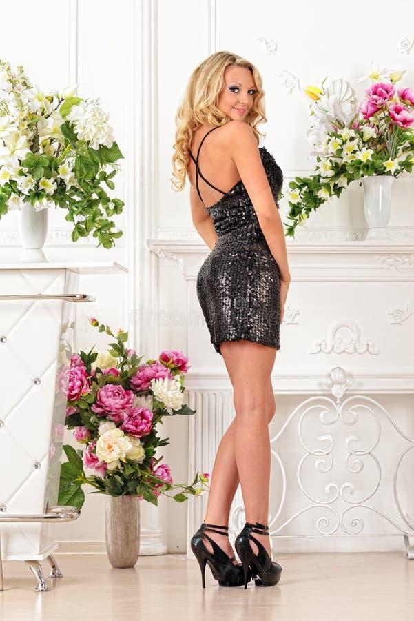 Schönheit im schwarzen Kleid im Luxusstudio. lizenzfreies stockbild