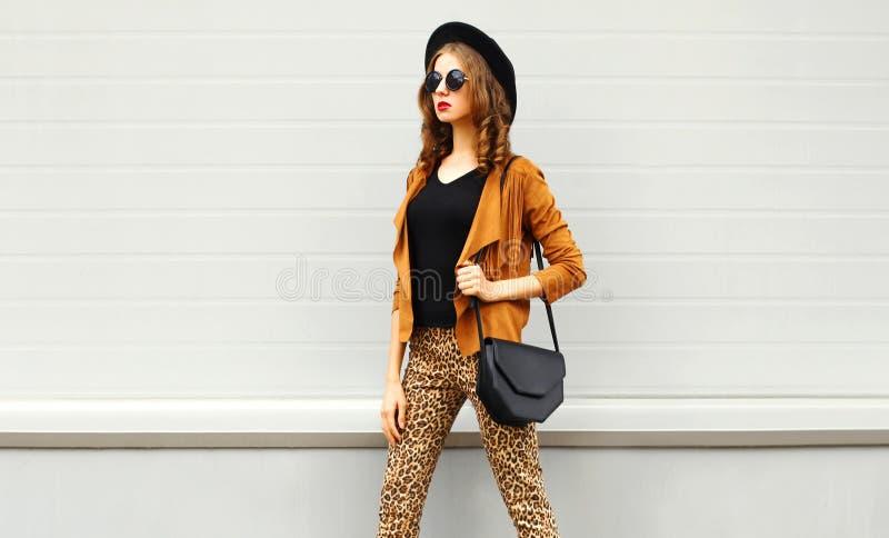 Schönheit im schwarzen runden Hut, Sonnenbrille, braune Jacke lizenzfreie stockfotografie