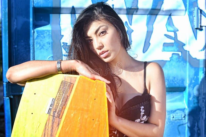 Schönheit im schwarzen weißen Kleid, langes Haar, das mit wakeboad auf dem bacground blauen Eisen, Graffiti steht lizenzfreies stockfoto