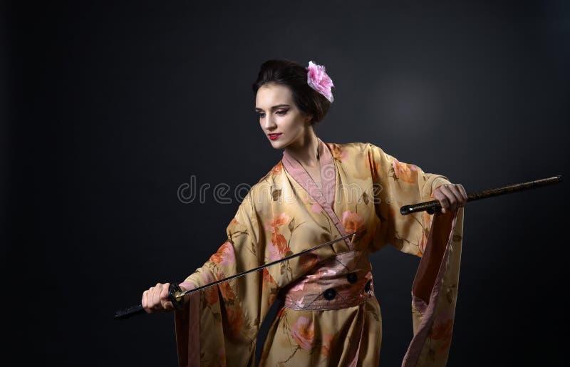 Schönheit im traditionellen japanischen Kimono mit katana stockfotografie