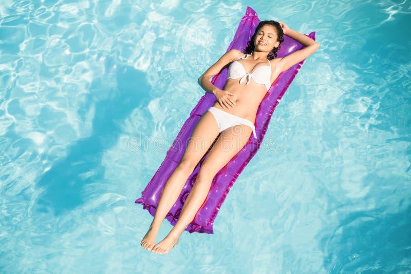 Schönheit im weißen Bikini, der auf Luftbett im Pool sich entspannt lizenzfreie stockfotos