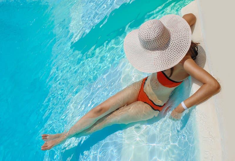 Schönheit im weißen Hut steht nahe dem Pool still lizenzfreie stockbilder