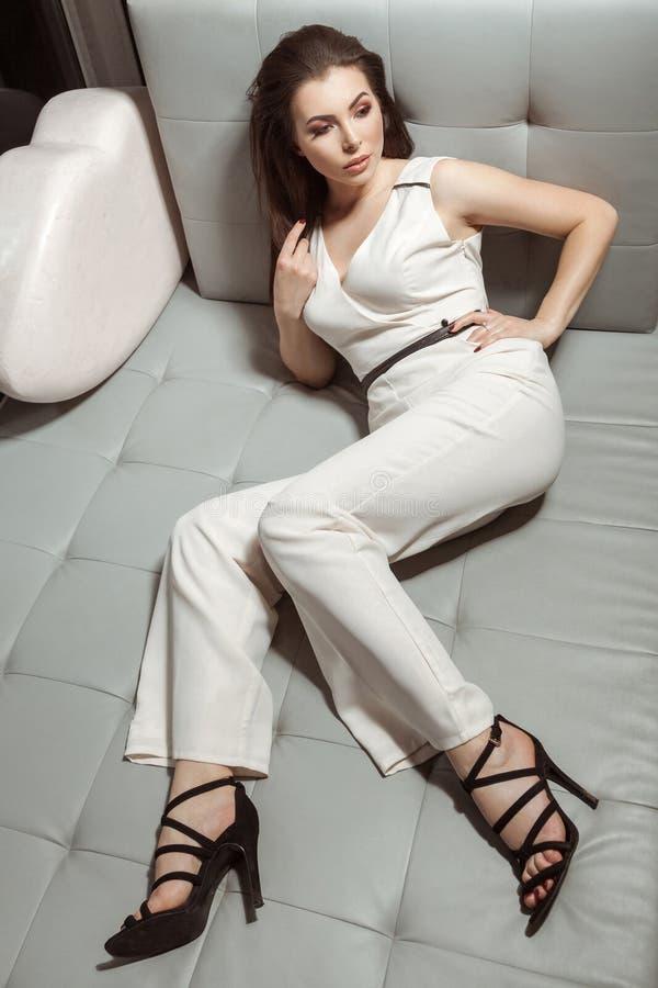 Schönheit im weißen stilvollen klassischen Overall, der auf Le sich entspannt stockfoto