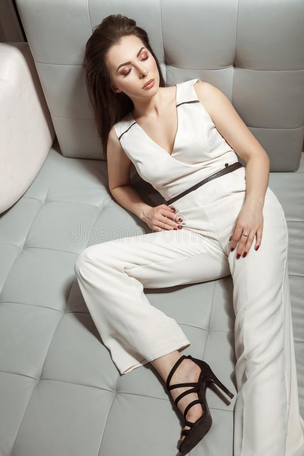 Schönheit im weißen stilvollen klassischen Overall, der auf Le sich entspannt stockfotografie