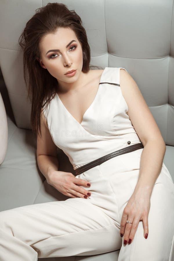 Schönheit im weißen stilvollen klassischen Overall, der auf Le sich entspannt lizenzfreie stockbilder