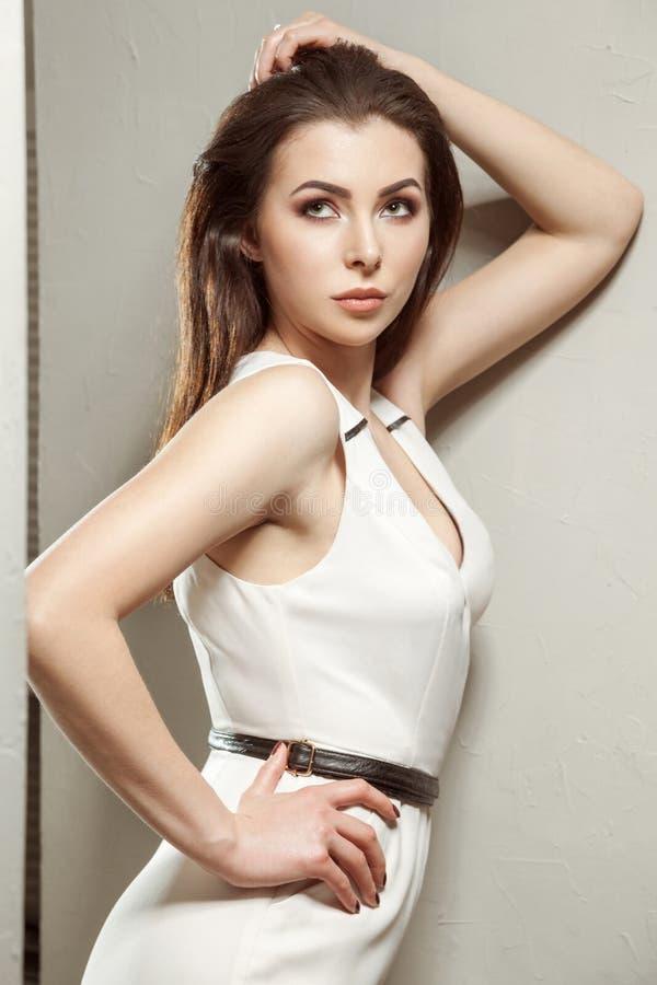 Schönheit im weißen stilvollen klassischen Overall, der auf ligh aufwirft lizenzfreie stockfotos
