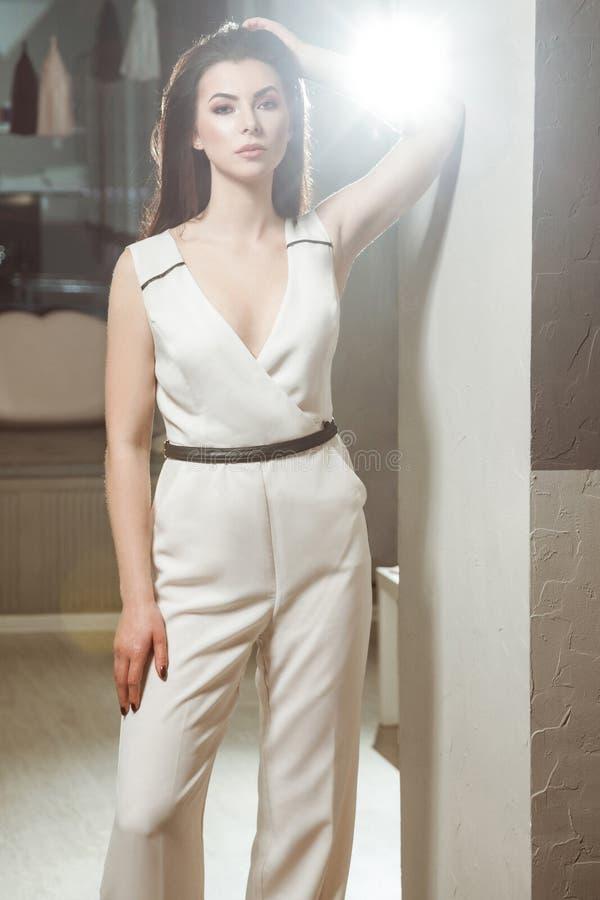 Schönheit im weißen stilvollen klassischen Overall, der im Raum aufwirft stockbilder