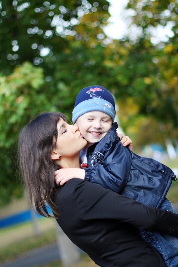 Schönheit küsst Mutter des Kindes an stockbilder