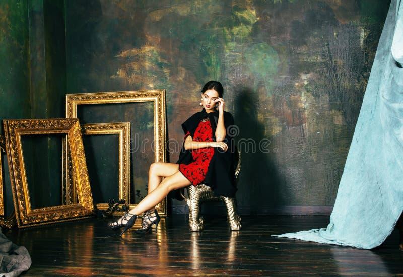 Schönheit kleidet reiche Brunettefrau in den Luxusnahen leeren Innenrahmen, tragende Mode, Lebensstilleutekonzept stockfotografie
