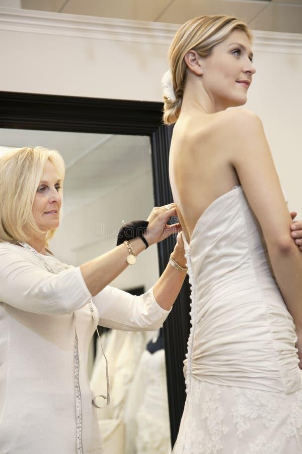Schönheit kleidete oben im Hochzeitskleid während der ältere Inhaber an, der im Brautspeicher hilft lizenzfreie stockfotografie