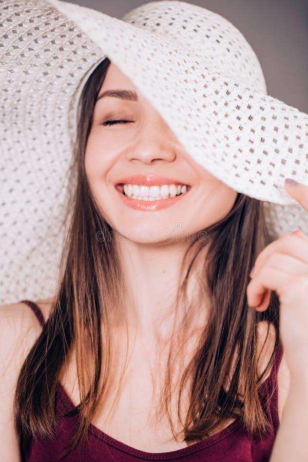 Schönheit in lächelndem reizend Lächeln des beige Hutes, Abschluss herauf Porträt stockbild