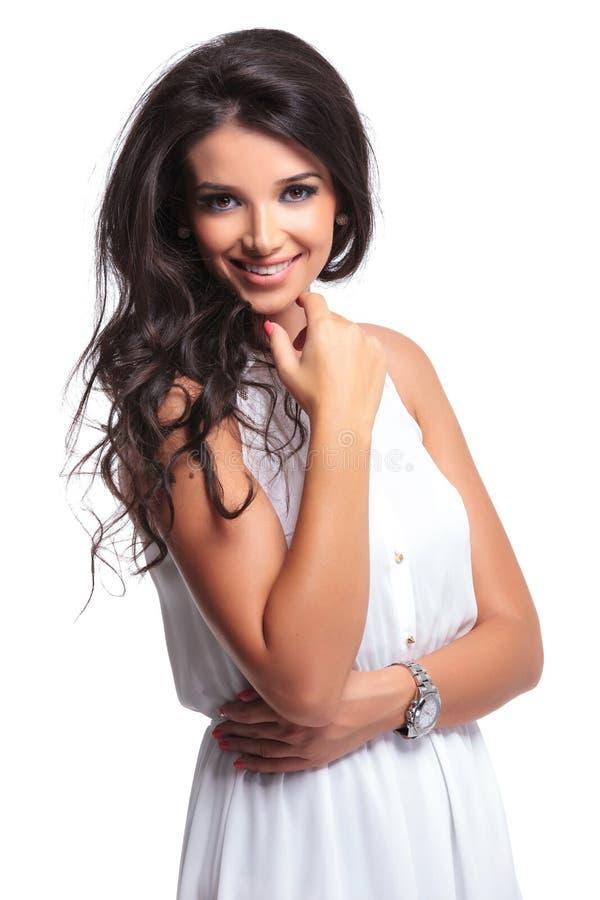 Schönheit lächelt mit der Hand auf Kinn stockfotografie