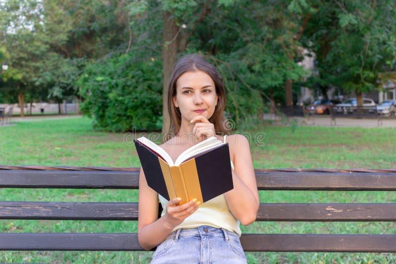 Schönheit liest ein Buch und denkt an etwas auf der Bank im Park Mädchen hat einige Gedanken und Ideen lizenzfreies stockbild