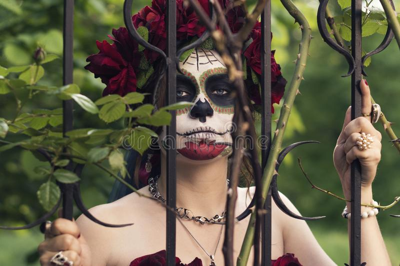 Schönheit Make-up im traditionellen Mexikaner Calavera-Zuckerschädel auf dem Hintergrund eines Eisenzauns mit Spitzen Tag der Tot lizenzfreie stockfotos