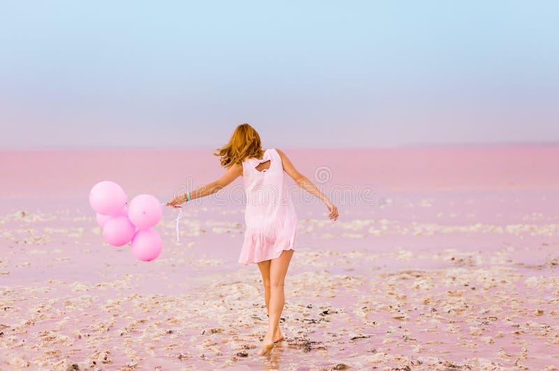 Schönheit mit baloons auf rosa Salzsee stockfotos